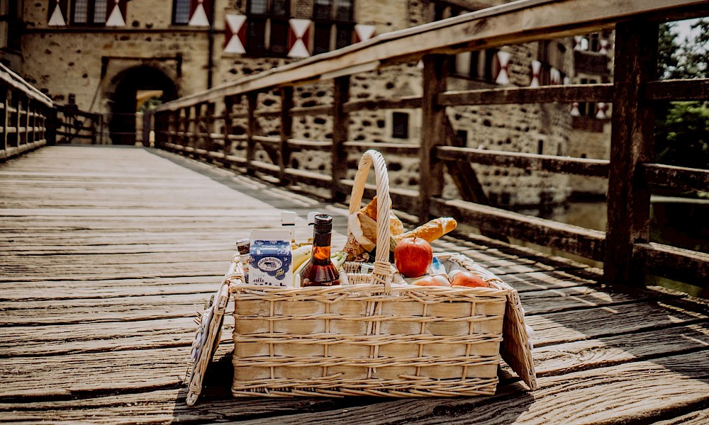 Ein gepackter Picknickkorb vor Burg Vischering