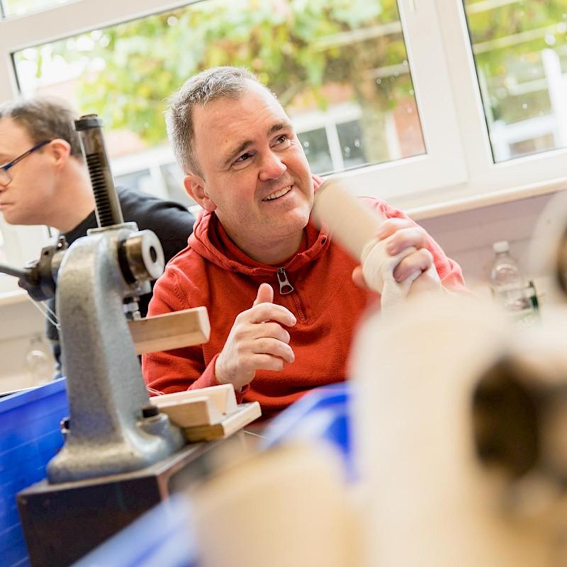 In Behindertenwerkstätten im Münsterland trennen die Mitarbeiterinnen und Mitarbeiter das Garn von der Pappspule.<br>© Velener Textil GmbH